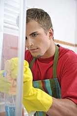 junger Mann putzt Dusche aus Glas
