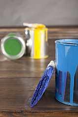 Blaue Lackdose und Pinsel auf Holzuntergrund
