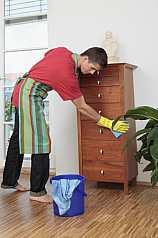 Mann putzt Möbelstück