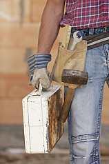 Männlicher Bauarbeiter mit Werkzeug und Metallkoffer vor Ziegelsteinmauer