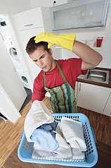 Mann steht verwundert vor Wäschekorb