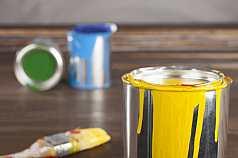 Gelber Farbeimer vor Malutensilien auf Holzuntergrund